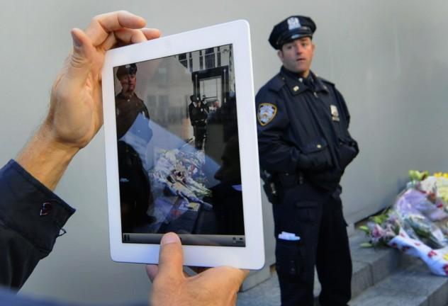 Homem usa iPad para fotografar policial em Nova York (Timothy A. Clary - 6.out.2011/AFP)